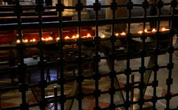Lit candles in a cell inside a church Royalty Free Stock Images