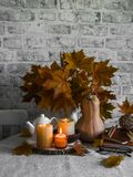 Lit candles, dry maple leaves, pumpkin, stack of books - autumn still life interior decoration house. Cozy home concept