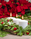 Lit candles with evergreens and poinsettias Stock Photo