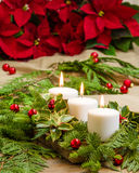 Lit candles with evergreens and poinsettias Stock Photos