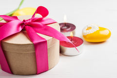 Lit candles and gift box with red ribbon Royalty Free Stock Images