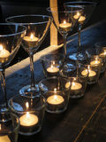 Lit candles in glasses on rustic wooden Royalty Free Stock Images