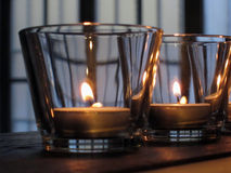 Lit candles in glasses on rustic wooden Stock Photo