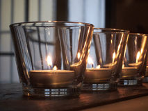 Lit candles in glasses on rustic wooden Royalty Free Stock Image