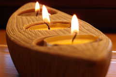 Lit candles in a holder. Candles in a boat shaped candle holder Royalty Free Stock Photos