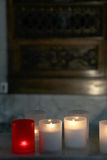 Lit candles inside a church, detail. A detailed view of some lit candles inside a church, with the altar blurred in the background, some space for tesxt on top Stock Photo