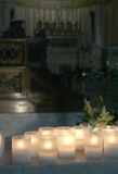 Lit candles inside a church. A detailed view of some lit candles inside a church, with the altar blurred in the background, portrait cut Royalty Free Stock Photography