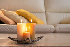 Lit candles on a marble table. And in the background a sofa with pillows, which Royalty Free Stock Photo