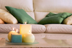 Lit candles on a marble table. And in the background a sofa with pillows, which Royalty Free Stock Photos