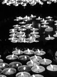 Lit candles at mass in church. Many lit candles at mass in church in black and white Stock Image