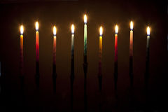 Lit Candles on a Menorah Isolated on Brown Background Royalty Free Stock Photography