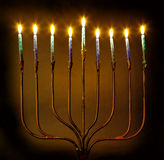 Lit Candles on a Menorah Isolated on Brown Background Royalty Free Stock Image