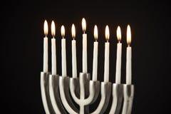 Lit Candles On Metal Hanukkah Menorah Against Black Studio Background royalty free stock photos