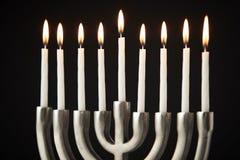 Lit Candles On Metal Hanukkah Menorah Against Black Studio Background stock images