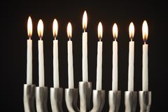 Lit Candles On Metal Hanukkah Menorah Against Black Studio Background stock photos