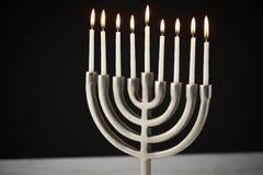 Lit Candles On Metal Hanukkah Menorah On Marble Surface Against Black Studio Background stock photography