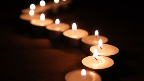 Lit candles in a row at night.  stock footage