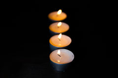 Lit candles in a row Royalty Free Stock Images