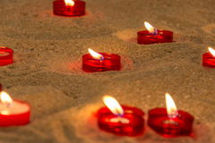 Lit candles on sand in a church to pray for people who died Stock Image