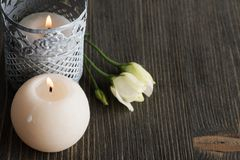 Lit candles and white flowers on dark rustic table royalty free stock images