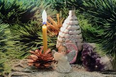 Lit Christmas candle, angel figurine with flute, Christmas tree decoration, amethyst and pine cones against background of green royalty free stock photo