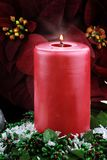 Lit Christmas Candle and Poinsettias Stock Image