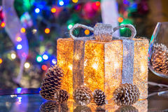 Lit Christmas present under a Christmas tree with defocused ligh Stock Photo