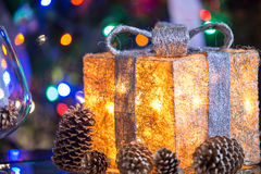 Lit Christmas present under a Christmas tree with defocused ligh Stock Photos