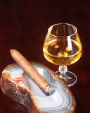 Lit cigar and after dinner liquor Stock Photos