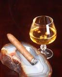 Lit cigar and after dinner liquor Stock Photos