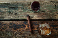 Lit cigar, wine and whiskey on a wooden background from above Stock Photos