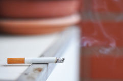 Lit cigarette. One lit cigarette with smoke Stock Photo
