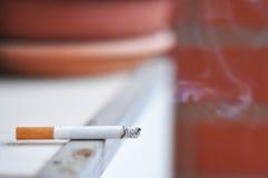 Lit cigarette. One lit cigarette with smoke stock photo
