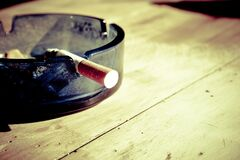 Lit Cigarette in Ashtray Royalty Free Stock Images