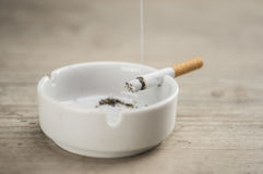 Lit cigarette in ashtray. Lit cigarette burning in ashtray close up Royalty Free Stock Image
