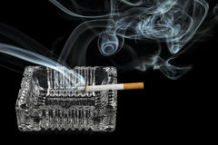Lit cigarette. On ashtray with smoke on black Royalty Free Stock Photography