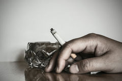 Lit cigarette between fingers Stock Photos