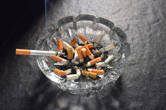 Lit cigarette with smoke lying on an ashtray. Filled with cigarette butts and ashes Royalty Free Stock Photo