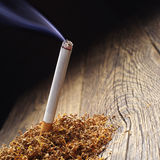 Lit cigarette and tobacco Royalty Free Stock Photo