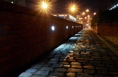 Lit and cobblestone alley at night Royalty Free Stock Images