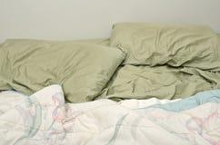 Lit désordonné, oreillers et couvertures Images libres de droits