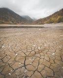Lit d'assèche au lac Kruth-Wildestein en automne avec le fond sec criqué du lac images libres de droits