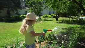 Lit de fleurs mignon de l'eau de petite fille avec le pulvérisateur d'arroseuse de tuyau Mouvement de cardan banque de vidéos