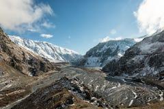 Lit de la rivière dans la vallée parmi les montagnes couronnées de neige Ciel bleu sur le fond des crêtes couronnées de neig image stock