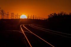 Lit de las pistas de ferrocarril durante una puesta del sol de oro del verano foto de archivo
