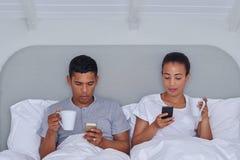 Lit de téléphone portable de couples Photographie stock