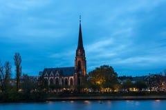 The lit Dreikoenigskirche next to the river Main Stock Photography