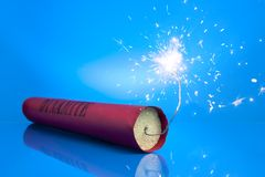 Lit dynamite stick on a blue background Stock Photography