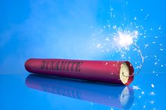 Lit dynamite stick on a blue background Royalty Free Stock Image