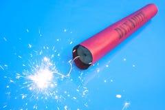 Lit dynamite stick on a blue background Stock Image